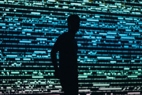 Anonymous figure in front of digital wall of data