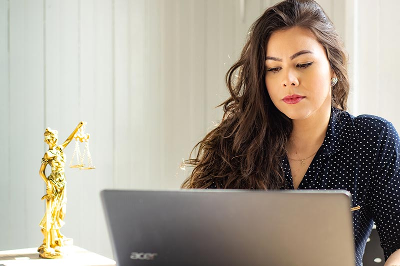 Lawyer at laptop with justice figure